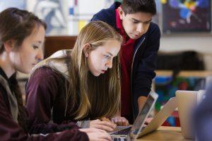 học sinh trung học làm bài luận trên laptop
