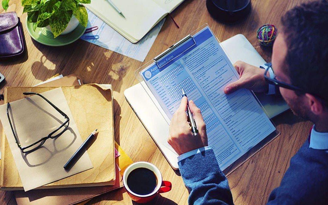 Một tay cầm bút một tay cầm hồ sơ du học Mỹ